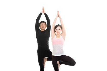 anjali: Two sporty people practice yoga in pair, couple doing exercise for spine, standing in Vrikshasana Pose, hands in Anjali mudra above the head