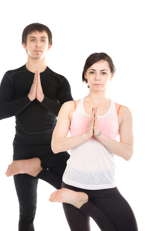 vriksasana: Two sporty people practice yoga with partner, couple doing exercise for spine, standing in Tree Pose, asana Vriksasana, leg in half lotus position, hands in Namaste Stock Photo