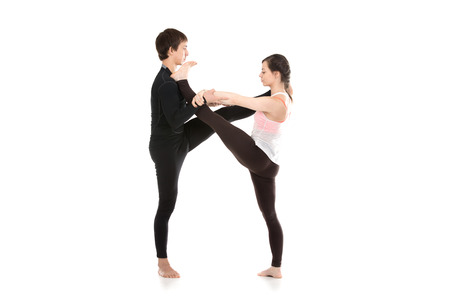 hasta: Two sporty people practice yoga in pair, fit couple doing acroyoga, stretching exercise, Extended Hand to Big Toe yoga pose, Utthita Hasta Padangushthasana