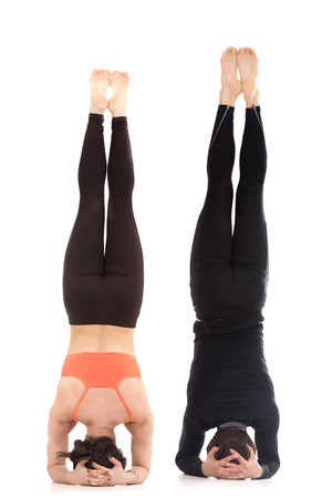 Two sporty people practice yoga in pair, acroyoga, fit couple doing supported headstand yoga asana, salamba sirsasana, Pose for Depression, back view