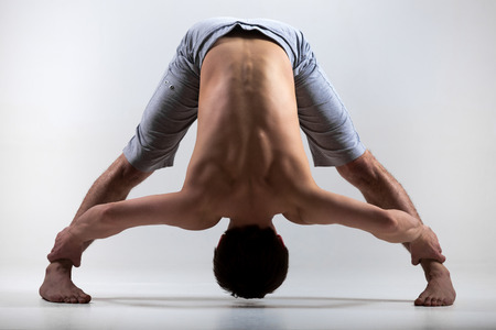 yogi: Sporty young man working out, yoga, pilates, fitness training, standing in asana Wide-Legged Forward Bend, Prasarita Padottanasana posture Stock Photo