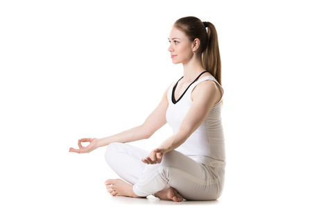 sukhasana: Portrait of young beautiful girl in white sportswear doing yoga practice, sitting cross-legged in sukhasana (Easy Pose), three quarters view, studio shot, isolated Stock Photo