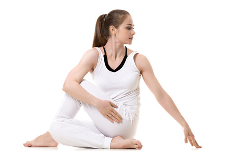 Young fitness model in white sportswear doing yoga or pilates training, Half lord of the fishes pose, Ardha Matsyendrasana, side view, studio shot, isolated