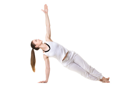 pilates studio: Young fitness model in white sportswear doing yoga or pilates training, Side Plank Pose, Vasisthasana, front view