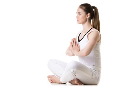 sukhasana: Portrait of young beautiful girl in white sportswear doing yoga practice, sitting cross-legged in sukhasana (Easy Pose) with hands in Namaste, three quarters view, studio shot, isolated
