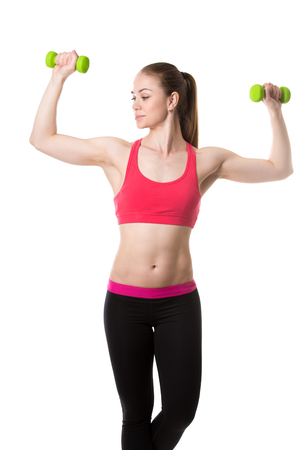 flexed: Healthy lifestyle: portrait of young sporty girl doing biceps training, holding dumbbells in flexed arms, studio shot, white background, isolated