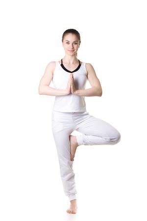 Full length portrait of young fitness model in white sportswear doing yoga or pilates training, Vrikshasana, Tree Pose, hands in Namaste, front view, studio shot, isolated Stock Photo