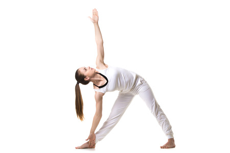 trikonasana: Beautiful fitness model practices yoga or pilates, standing in Triangle yoga pose, Trikonasana, stretching exercise, front view Stock Photo