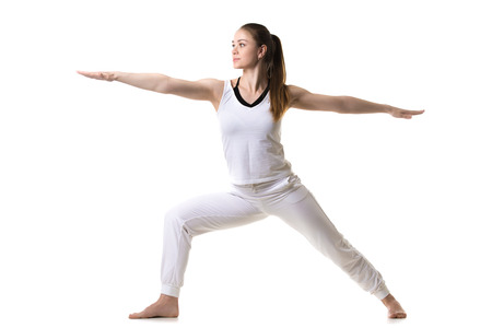 Beautiful fitness model practices yoga or pilates, doing lunge exercise, standing in Warrior II posture, Virabhadrasana 2, side view, studio shot, isolated