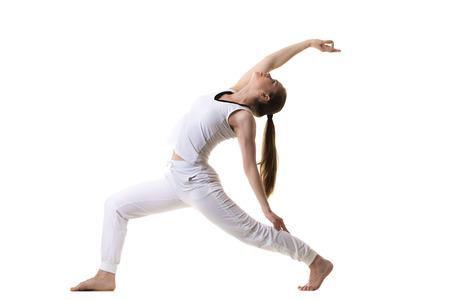 guerrero: Modelo de la aptitud hermosa practica yoga o pilates, haciendo ejercicio de la estocada, de pie en Guerrero inversa Pose, la variaci�n de la Media Luna, Viparita Virabhadrasana, vista lateral, tiro del estudio, aislado