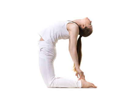 ushtrasana: Young fitness model in white sportswear doing yoga or pilates training, asana Ustrasana (Camel yoga Pose), side view, studio shot, isolated Stock Photo