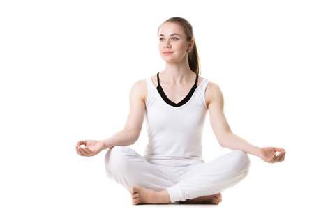 Portrait of young beautiful girl in white sportswear doing yoga practice, sitting cross-legged in sukhasana (Easy Pose), front view, studio shot, isolated