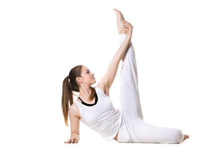 pilates studio: Portrait of young beautiful girl in white sportswear doing yoga or pilates practice, stretching exercises for legs, side view, studio shot, isolated