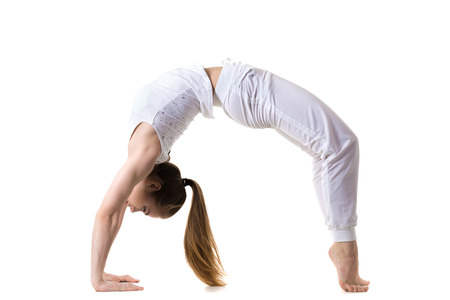 Young fitness model in white sportswear doing yoga or pilates training, exercise bridge, urdhva dhanurasana, Upward Bow (Wheel) yoga Pose, side view