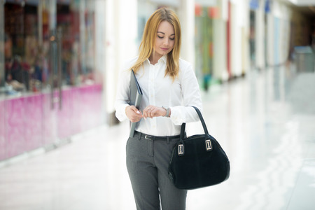 errands: Beautiful business girl wearing office style outfit holding document dossier and suede bag, looking at wristwatch, checking time, running late or waiting