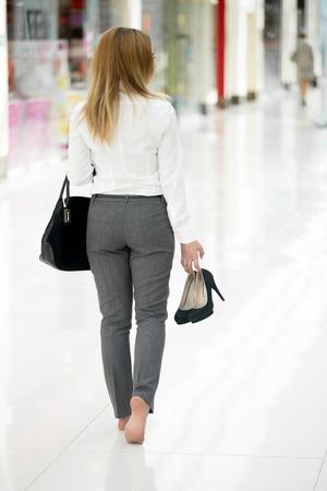 현대적인 건물에 맨발로 걷기 손에 그녀의 높은 뒤꿈치 신발을 들고 사무실 스타일의 옷에 젊은 여자, 다리 근접