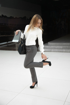 uncomfortable: Beautiful young woman in office style white shirt holding black document folder and leather bag, touching her high heel shoe, feeling uncomfortable Stock Photo
