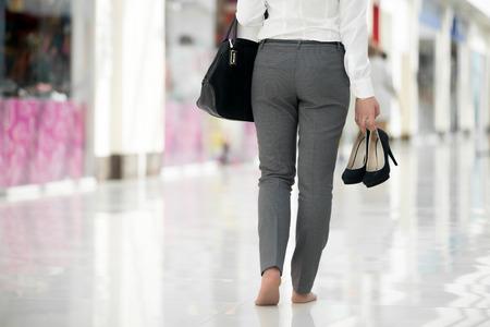 agotado: Mujer joven en ropa de estilo de oficina que llevan en la mano los zapatos de tacón alto, caminando descalzo en edificio contemporáneo, las piernas de cerca