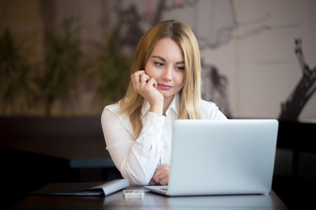 Young beautiful blond caucasian business woman working on laptop, looking at screen with thoughtful expression, cellphone and black folder lying on the table photo