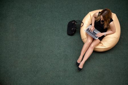 typing: Joven mujer sentada en bolsa de frijoles que trabaja en la computadora port�til en la zona wifi p�blica, mecanograf�a, vista desde arriba, copia espacio