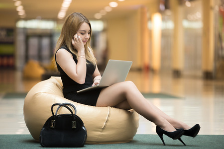 Young serious female sitting on bean bag working on laptop in public wifi area, typing, wearing short black dress, high heel shoes, making call, talking on cellphone in shopping center