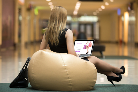 Young female wearing short black dress, high heel shoes sitting on bean bag using laptop in public wifi area, ordering online with electronic app, signing in on website, rear view