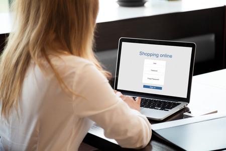 cafe internet: Compras de la muchacha en línea en la computadora portátil, el uso de la tienda en línea, compras a través de la aplicación electrónica, la firma en el sitio web, de cerca, de visión trasera Foto de archivo