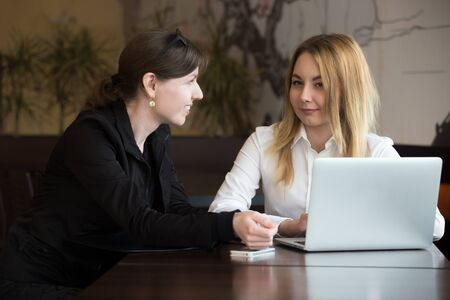Two young caucasian women sitting at the table on business meeting, talking, working together, making decision beside laptop Stock Photo