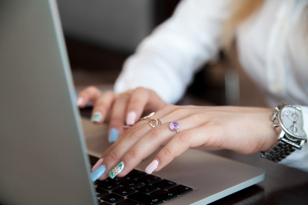 shopping order: Modern office girl hands on laptop using touch pad and keyboard with rings on fingers and colorful manicure, close up