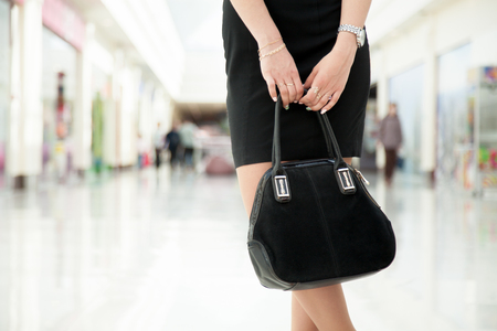 Attractive young woman wearing little black dress holding suede handbag in outlet, close-up