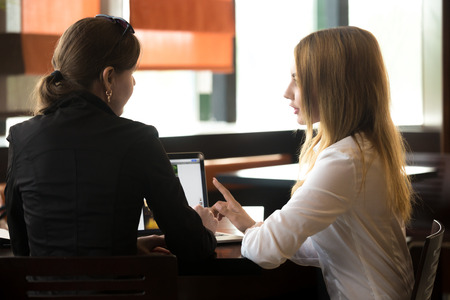Two young caucasian office women meeting, discussing business, sitting at the table, beside laptop, rear view