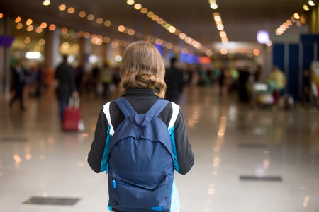 alone girl: Young woman in 20s with backpack walking in airport terminal, wearing casual style clothes, rear view