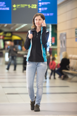 Full length portrait of smiling young woman in 20s with backpack waiting for flight, walking in modern airport terminal, using cell phone making call, blurred electronic panel on background photo