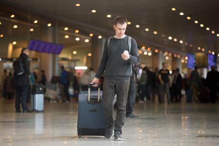 若い現代空港ターミナルに歩いて 20 代でハンサムな男の笑みを浮かべて、公共の wifi でスマート フォンのアプリを使用して領域、テキスト メッセ