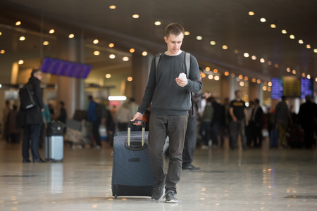 airport: Young smiling handsome man in 20s walking in modern airport terminal, using smart phone app in public wifi area, texting, travelling with luggage bag, wearing casual style clothes Stock Photo