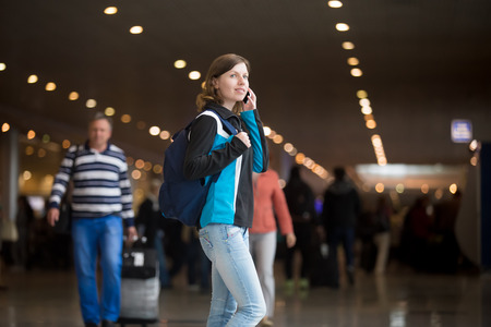 Portrait of smiling young woman in 20s with backpack walking in airport terminal, using cell phone, making call, wearing jersey and jeans, blurred crowd of travelling people on the background photo