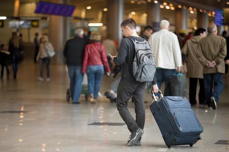 Jonge knappe reiziger in 20s wandelen in de moderne terminal van de luchthaven, met behulp van smartphone-app in de openbare wifi gebied, messaging, reist met de bagage tas, dragen casual stijl kleding, kopiëren ruimte