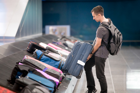 airport lounge: Young handsome man passenger in 20s with carry-on backpack collecting his luggage at conveyor belt in arrivals lounge of airport terminal building