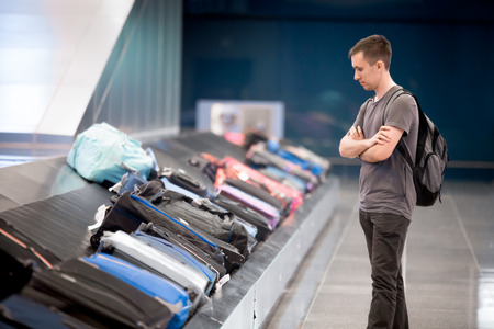 travel luggage: Young handsome man passenger in his 20s with carry-on backpack waiting at conveyor belt to pick his luggage in arrivals lounge of airport terminal building