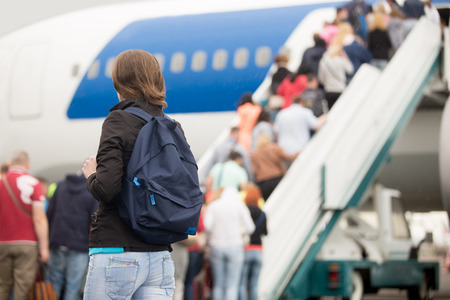 model airplane: Young woman passenger in 20s travelling with backpack, boarding airplane, people climbing ramp on background, rear view