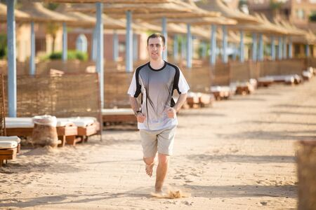 alongside: Healthy lifestyle: young sporty man working out outdoors, jogging on summer sunny empty beach, running fast alongside the row of sun loungers and umbrellas, sand flying under his feet