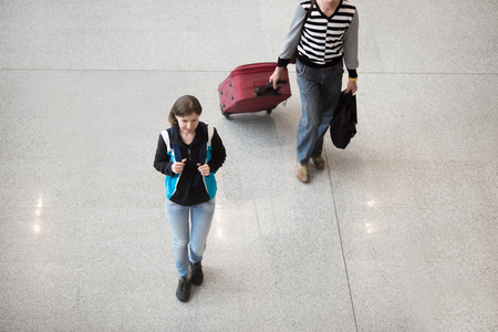 late 20s: Young smiling woman in late 20s walking with backpack in airport terminal, wearing casual style clothes, top view