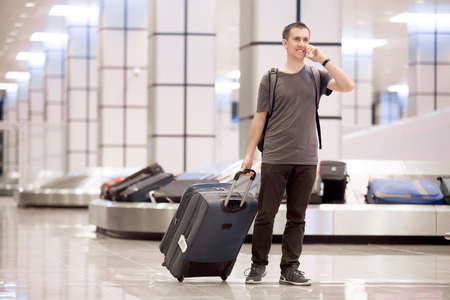 Full length portrait of young happy smiling handsome traveller man in 20s leaving arrivals lounge of airport terminal building after collecting his baggage at conveyor belt, talking on cellphone