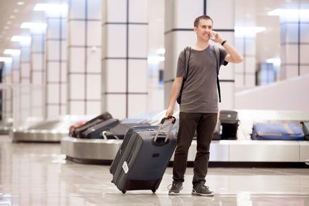 Volledige lengte portret van jonge gelukkig lachend knappe reiziger man in de jaren '20 verlaten aankomsthal van de luchthaven terminal gebouw na het verzamelen van zijn bagage op de transportband, praten over mobiel Stockfoto