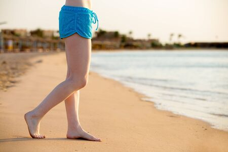 Young woman legs standing barefoot on the sunny sand beach at sea shore, relaxing in sunlight, copy space, close up Stock Photo