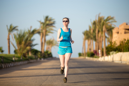 girl sport: Healthy lifestyle: morning sport practice of fit young woman in blue sportswear working out on the sunny summer street, jogging in tropics, wearing sunglasses Stock Photo