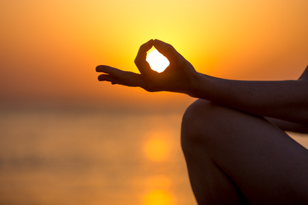 yoga meditation: Young woman fingers in yogic Jnana mudra, close up, copy space. Relaxation, meditation on sea at sunset or sunrise Stock Photo