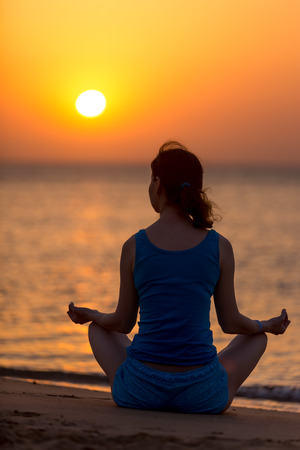 sukhasana: Serene young woman relaxing on the beach sitting with crossed legs in yoga Easy Pose, Sukhasana, meditating at sunset or sunrise, back view