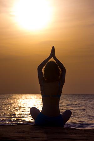 sukhasana: Silhouette of serene young woman practicing yoga, Sitting on the seashore at sunset or sunrise in asana Sukhasana, hands above head, back view