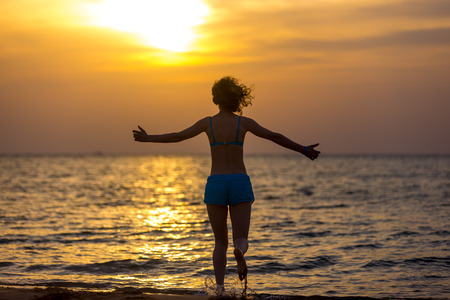 woman resting: Back view of young happy woman in blue swimwear running with stretched arms into the sea towards colorful sunrise or sunset sky, basking in warm sunlight, rising water splashes